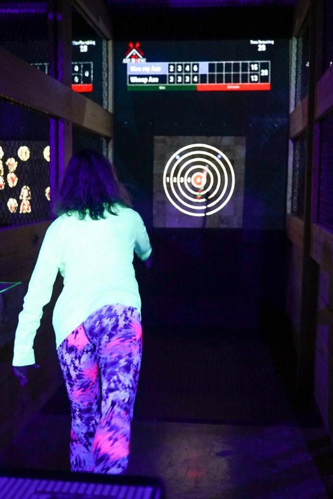 women under blacklight throwing axe
